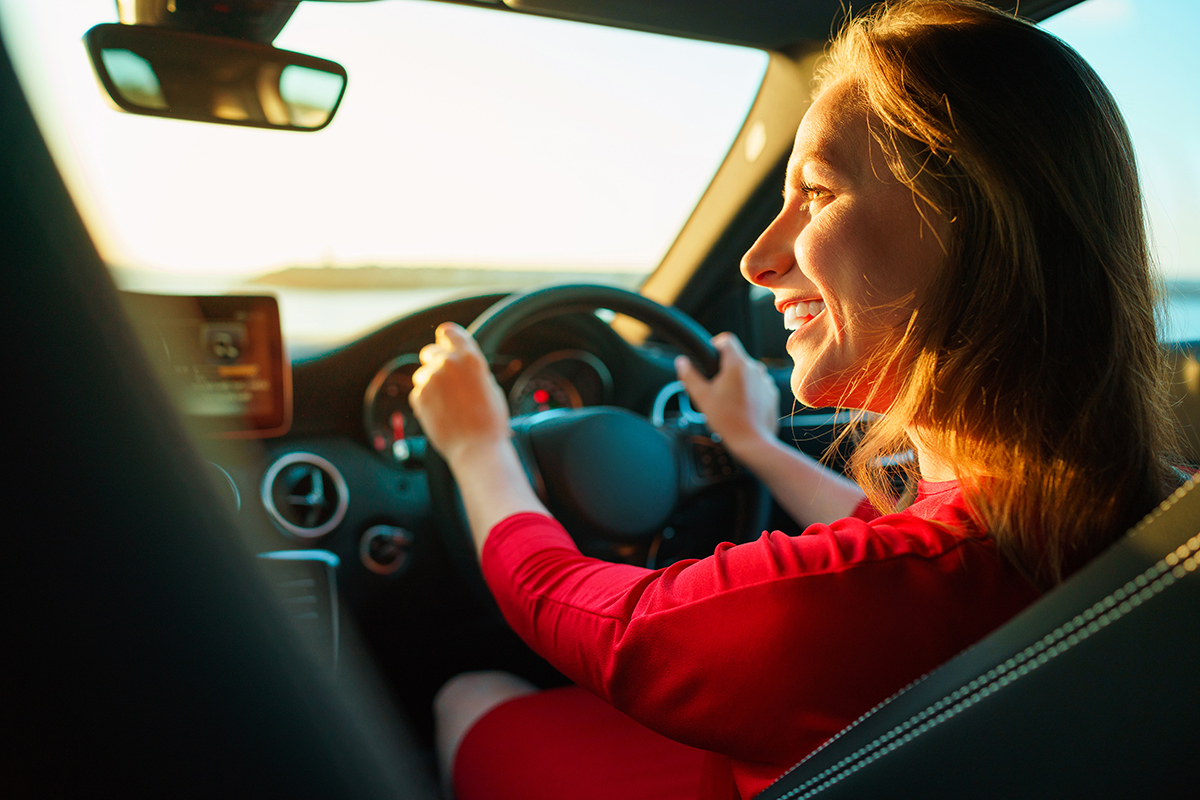 happy-woman-in-red-dress-driving-car-insurance